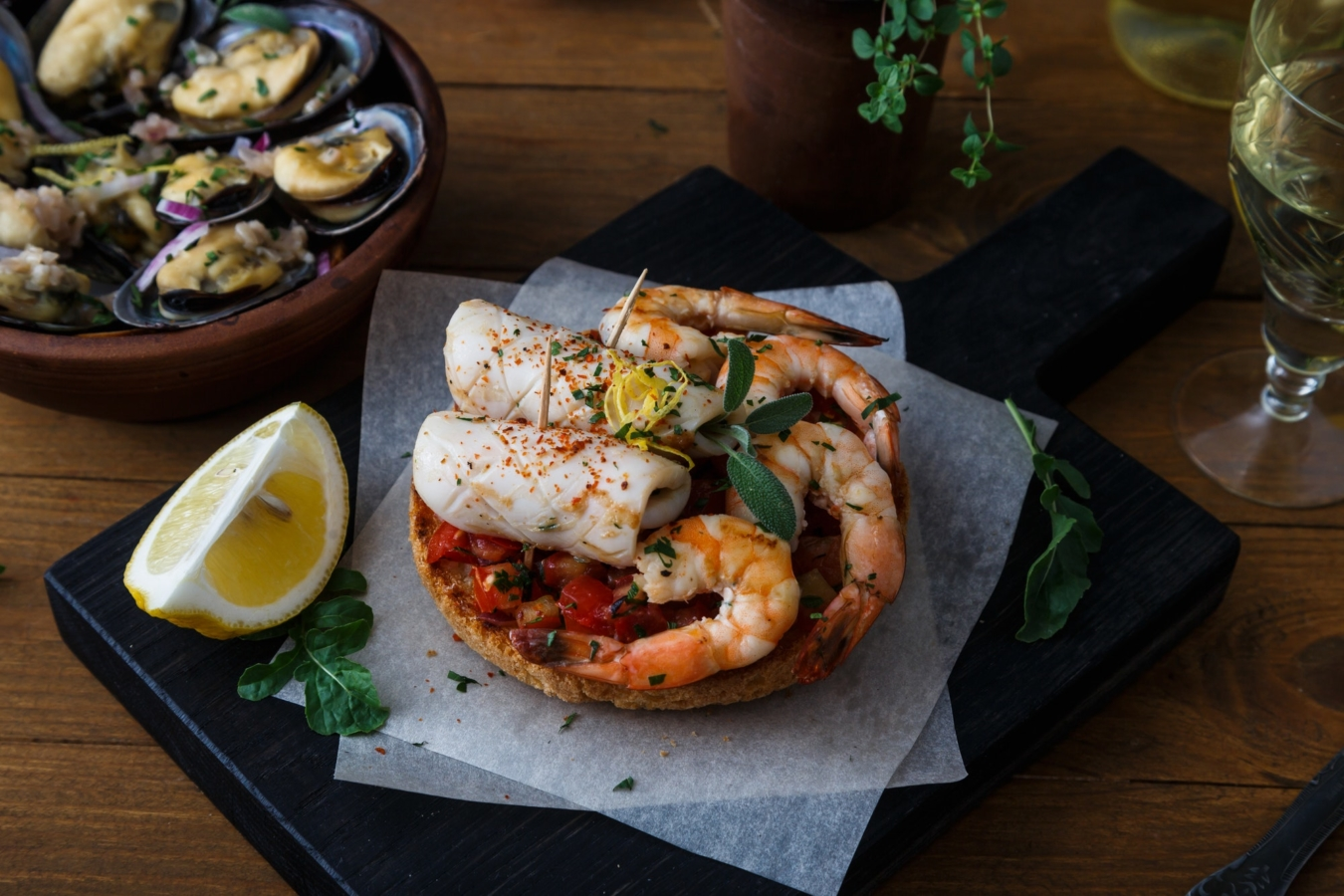 Tapas with shrimp and squid on wooden board, from top