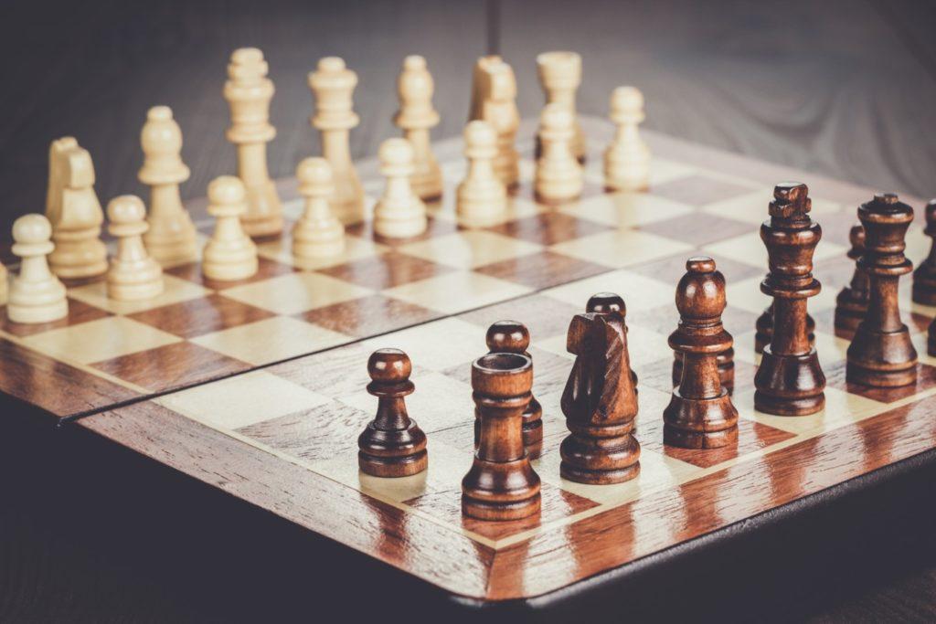 Schach-Brett mit Figuren auf Holztisch