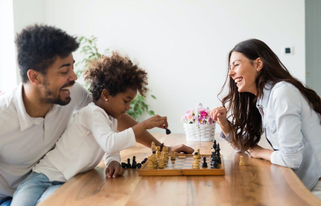 Glückliche Familie, die zu Hause zusammen Schach spielt